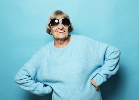 lifestyle and people concept - portrait of a content senior lady wearing blue sweater smiling and looking at the camera