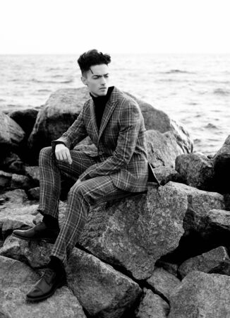 fashionable young man sitting on the rocks near the sea