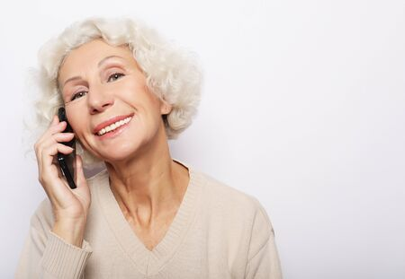 technology, communication age and people concept: happy senior woman with smartphone over white background