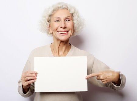 Aged woman with blank advertising board or copy space. Portrait of handsome expressive grandmother in lightbeige sweater. Indoor,studio shot, isolated on white background.