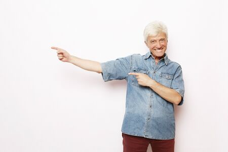 lifestyle, emotion and people concept - Happy senior man show something over white background