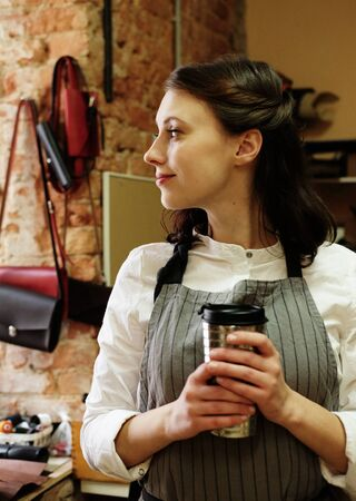 young master woman drinks coffee in a workshop, lunch break