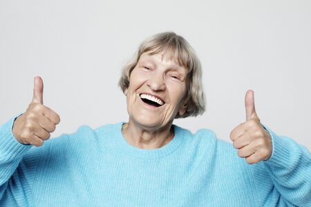 Elderly woman giving a thumb up and looking at the camera