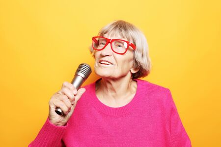lifestyle  and people concept: Portrait of funny grandmother holds up the microphone stand and sings   isolated on vivid yellow background