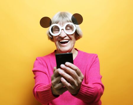 lifestyle, family  and people concept: old grandmother is talking to her grandchildren by phone, smiling and greeting them. Stock Photo