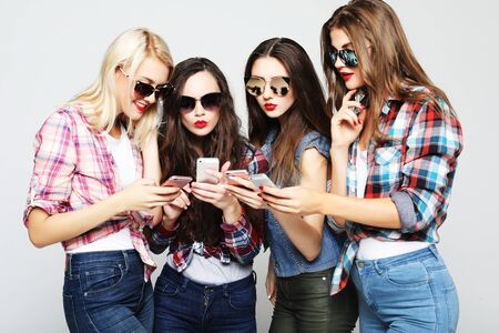 happy women friends sharing social media in a smart phone Stock Photo
