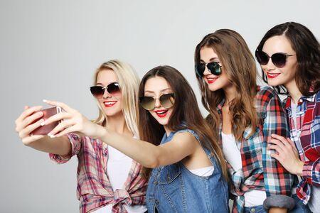 four happy teenage girls with smartphone taking selfie