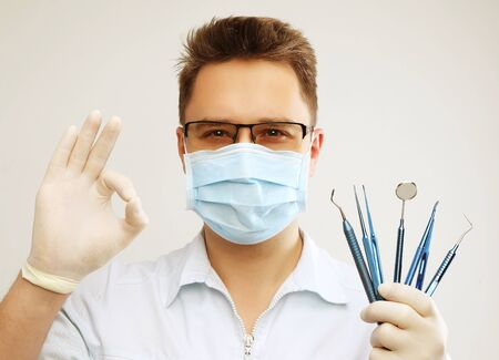 Dentist with dentistry tools isolated on grey backgound Stock Photo