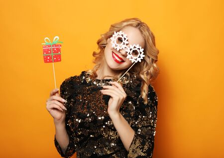 lifestyle, holiday and people concept - cheerful young woman in dress holds props for a party and smiles.