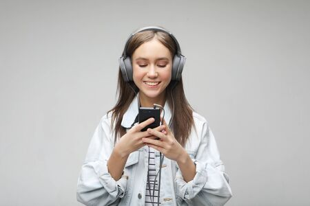 Beautiful young woman listening to music in headphones with smartphone Reklamní fotografie
