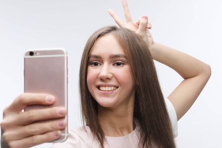 happy smiling young woman wearing taking selfie with smartphone