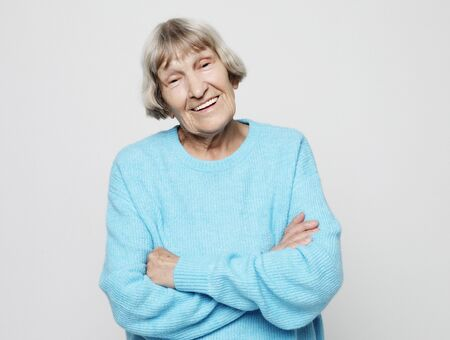 Lifestyle, emotion and people concept - portrait of a content senior lady wearing blue sweater smiling and looking at the camera
