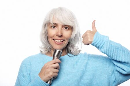 Lifestyle, emotion and people concept: Happy old senior woman singing with microphone, having fun, expressing musical talent over white
