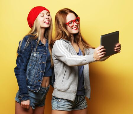 two hipster girls friends taking selfie with digital tablet Stock Photo