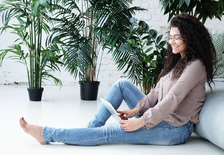lifestyle, tehnology and people concept - Portrait of an attractive young woman using a digital tablet at home Фото со стока