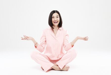 lifestyle, fashion, and people concept - beautiful brunette girl dressed in pink pajamas over white background Stockfoto