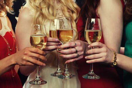 Concepto de estilo de vida, fiesta y personas - Grupo de chicas de fiesta tintineando flautas con vino espumoso, de cerca