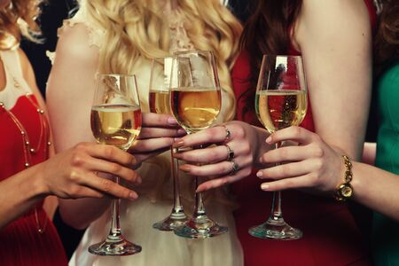lifestyle, party and people concept - Group of partying girls clinking flutes with sparkling wine, close up