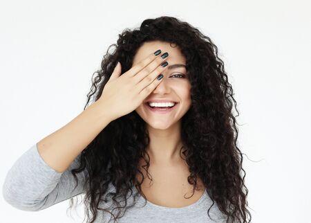 Concepto de estilo de vida, emoción y personas - mujer joven que cubre sus ojos con las manos sobre fondo blanco.