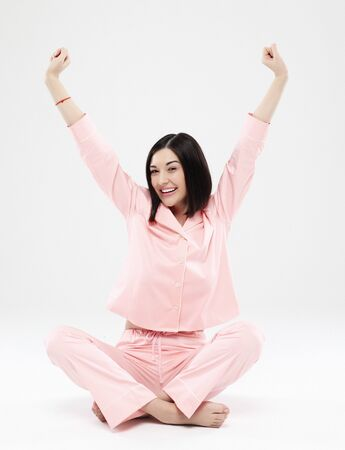 beautiful brunette woman dressed in pink pajamas sitting on the floor Stockfoto
