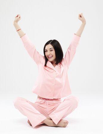 belle femme brune vêtue d'un pyjama rose assis sur le sol Banque d'images