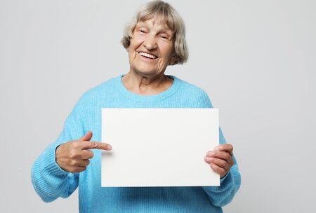 Aged woman with blank advertising board or copy spacet.