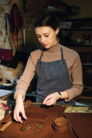 young brunette woman works in a bag making studio, cuts out details