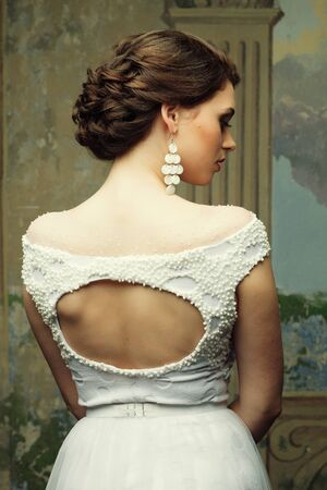 beautiful bride in a white dress and earrings, beauty and youth, happiness and innocence.