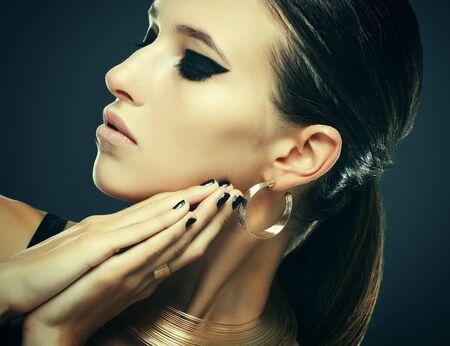 Bella donna con trucco da sera e gioielli in oro.