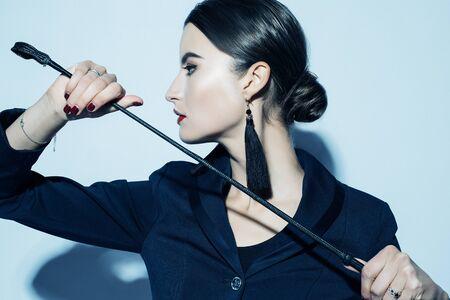 Sexy jeune belle dame dominante posant en tenue noire
