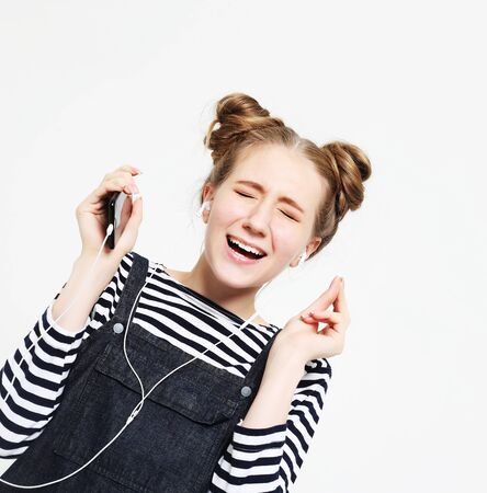 Beautiful woman in headphones listening to music on white background