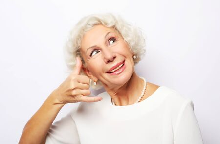 Lifestyle, emotion and people concept: Elderly happy woman is gesturing to call her with a hand