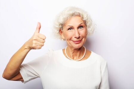 Lifestyle, emotion and people concept: Elderly happy woman giving a thumb up and looking at the camera