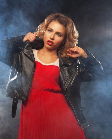 portrait of beautiful fashionable woman wearing red dress on dark background