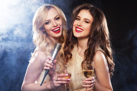 lifestyle, party and people concept - Karaoke party. Beauty girls with a microphone singing and dancing over dark background