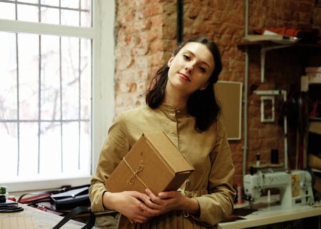young woman folds packing box in sewing workshop