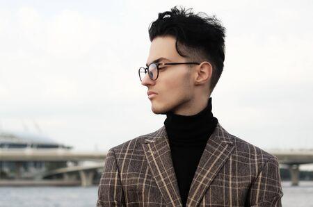 Elegant young handsome man. Outdoors fashion portrait.