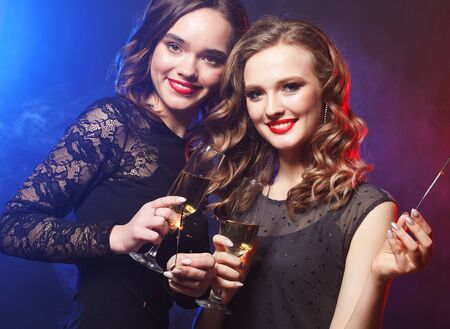 Two beautiful young women in black dress with wine glasses and sparkle fire. 스톡 콘텐츠 - 129244268