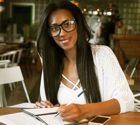Portrait of beautiful young black woman sitting at cafe and writ