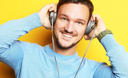 lifestyle and people concept: Happy young man listening to music with headphones over yellow background Stock Photo - 129245184