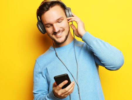 lifestyle and people concept: Happy young man listening to music with headphones over yellow background Stock Photo - 129245321