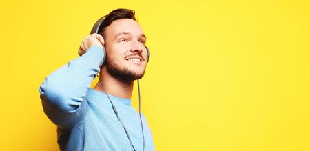 Handsome Man lictening to music over yellow background Stock Photo - 129245323