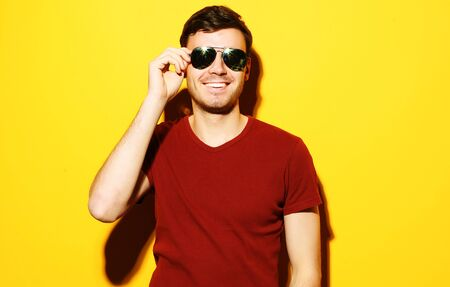 closeup portrait of a young casual man wearing sunglasses on yellow background