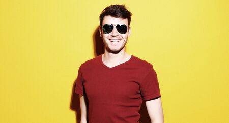 portrait of a young man wearing sunglasses on yellow background