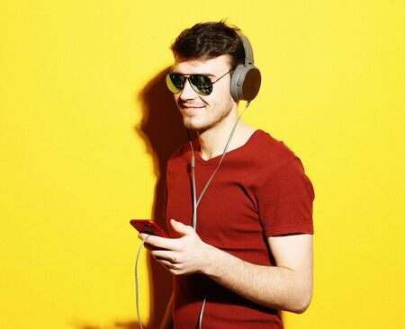 Music! Young man wearing headphones and holding mobile phone. Stock Photo - 129246028