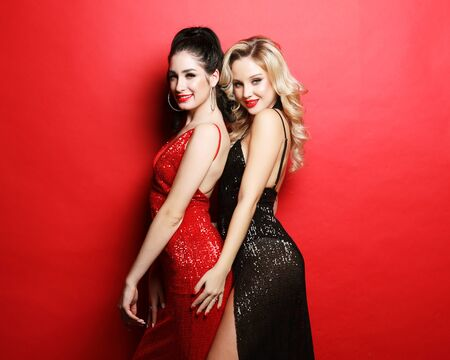 Two glamour women in luxury glitter sequins dress and bright visage posing over red background Stock fotó
