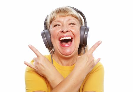 People, emotion and technology concept: portrait of senior woman listening to music with headphones Stock Photo - 129246688