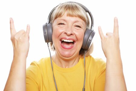 People, emotion and technology concept: portrait of senior woman listening to music with headphones Stock Photo