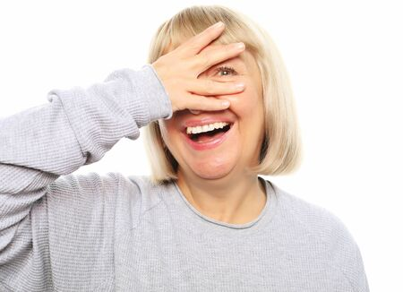 Funny old lady closes her eyes with her hand, peeps and laughs, isolated on white