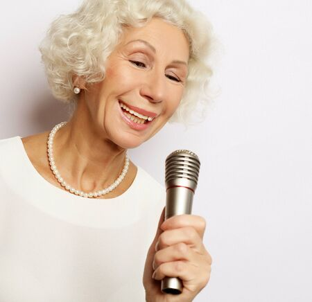 lifestyle and people concept: Portrait of charming modern grandmother holds up the microphone stand and sings